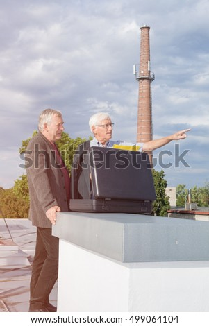 Two senior businessmen with briefcase discussing business outdoors on the roof of a building.