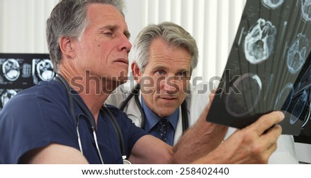 Two senior doctors working in the office - stock photo