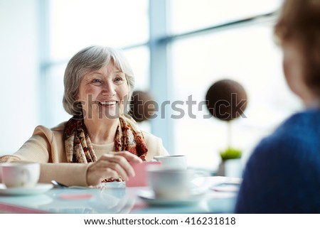 Two senior friends having a round of cards - stock photo