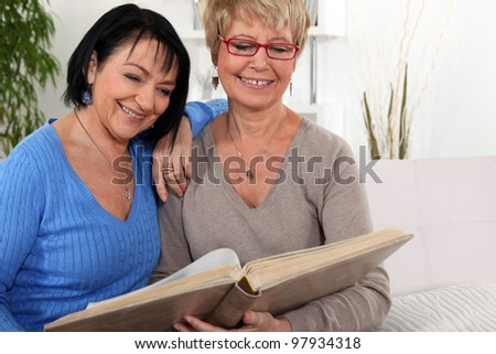 two senior friends looking at a photo album - stock photo