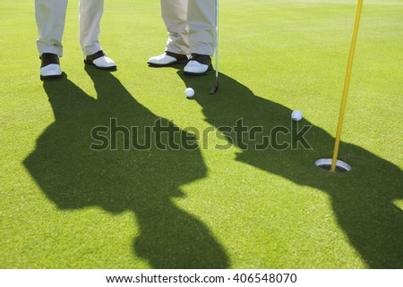 Two senior friends playing golf in summer day - stock photo