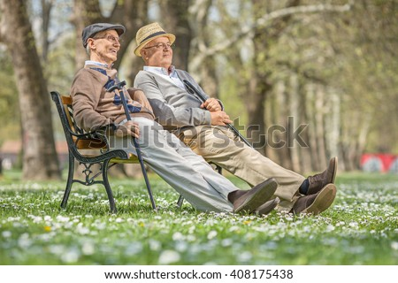 Two senior gentlemen sitting and relaxing on a wooden bench in a park on a sunny day - stock photo