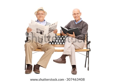 Two senior gentlemen sitting on a bench and holding a book and a newspaper isolated on white background - stock photo
