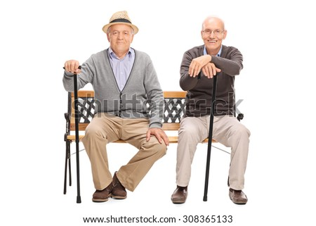 Two senior gentlemen with black canes sitting on a wooden bench and looking at the camera isolated on white background