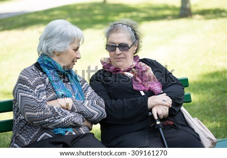 two senior ladies chatting friendly on a bench to the park
