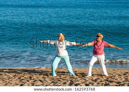 Two senior ladies doing yoga exercises on beach.  - stock photo