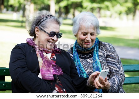 two senior ladies having fun with the technology of smartphone