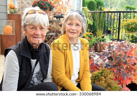 Two senior ladies,seated outside on a wood deck during autumn. - stock photo