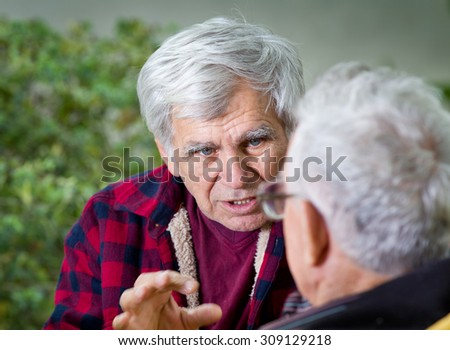 Two senior men sitting on bench in the park and talking