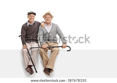 Two senior pals holding canes and sitting on a blank white signboard isolated on white background