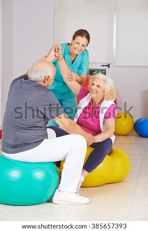 Two senior people doing physiotherapy in nursing home with a physiotherapist