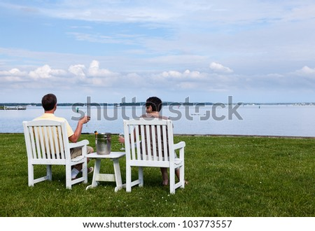Two senior people in patio chairs drinking champagne by Chesapeake bay