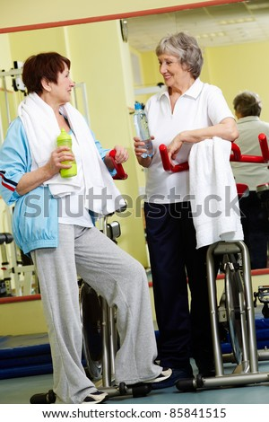 Two senior women communicating in gym - stock photo