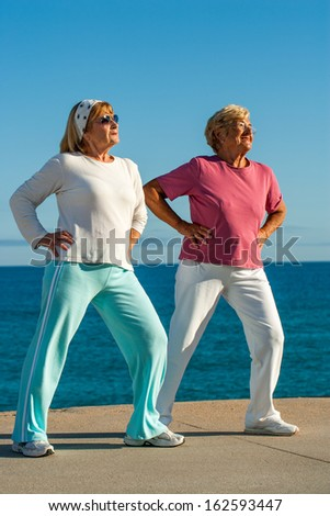 Two senior women doing leg stretching exercise at seafront.