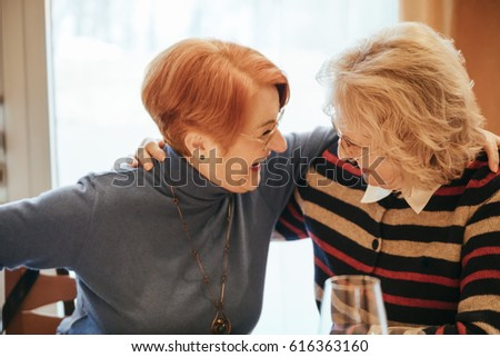 Two Senior Women In A Restaurant Laughing And Hugging