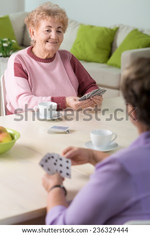 Two senior women playing cards in lounge - stock photo