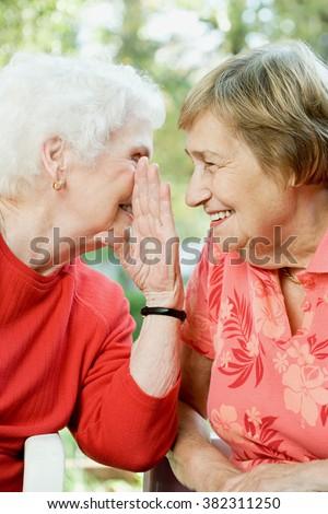 Two senior women sharing a secret - stock photo
