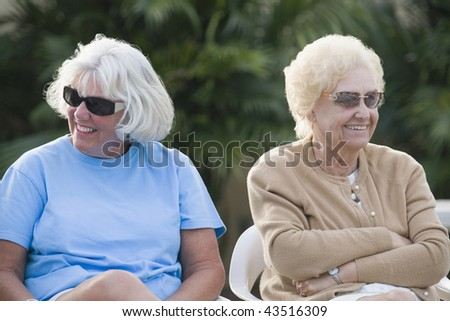 Two senior women sitting together and smiling - stock photo