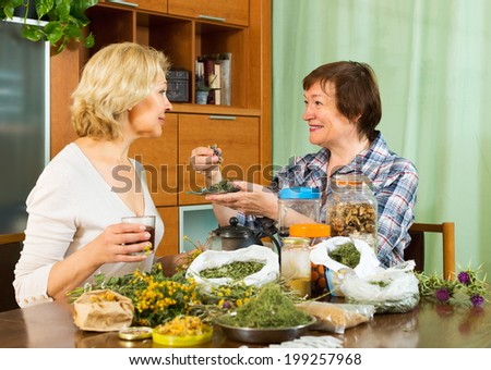 Two seniore pensioner sitting at the table with herbal tea and herbs