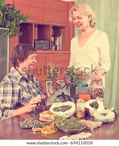 Two seniore positive women sitting at the table with herbal tea and herbs