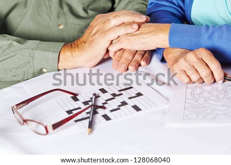 Two seniors holding their hands in a nursing home with riddles and glasses on table - stock photo
