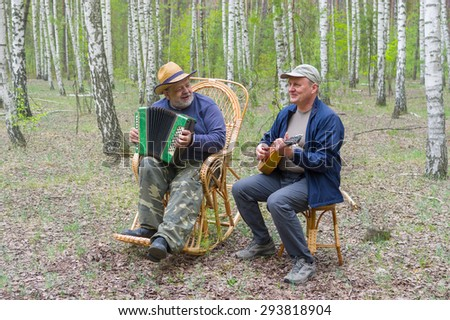 Two seniors playing music in birch forest