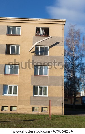 Two seniors throwing rolled carpet out of a window from the top floor of a building.