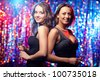 Two sensual women dressed in black posing against sparkling background - stock photo