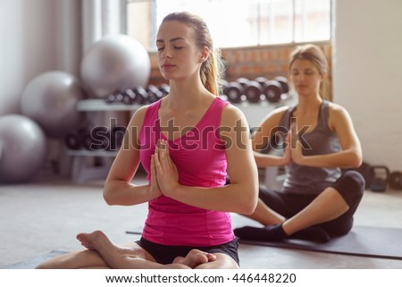 Two serene young woman doing meditation exercises in a gym sitting on yoga mats in the lotus position with closed eyes and clasped hands