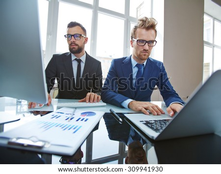 Two serious businessmen networking in office - stock photo