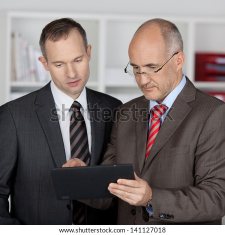 Two serious businessmen working with tablet computer - stock photo