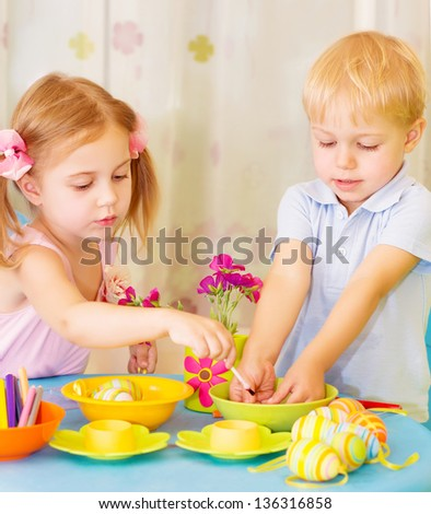 Two serious children paint Easter eggs at home, using colorful decoration, Christian holiday concept - stock photo