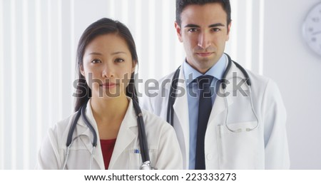 Two serious doctors looking at camera