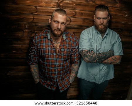 Two serious mans with beards and tattoos posing over wooden wall. - stock photo