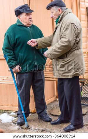 Two serious senior men talking in courtyard