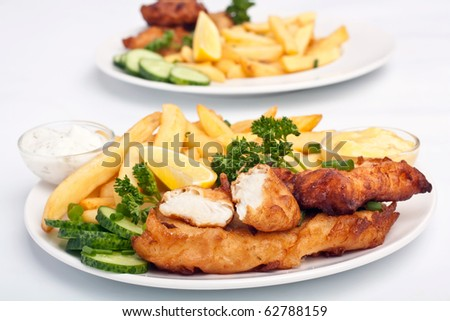 two servings of fish and chips on white background - stock photo