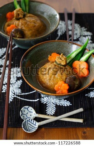 Two servings of shirataki and mochi kinchaku, a Japanese stuffed fried tofu beggar's purse braised in soy sauce garnished with carrot, shiitake mushroom and okra - stock photo
