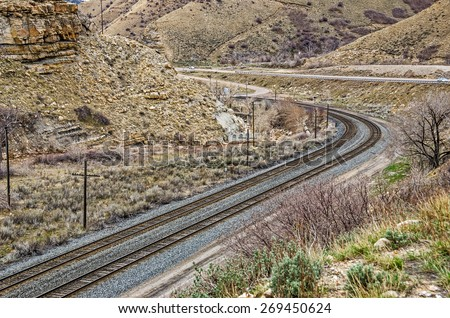 Two sets of tracks winding around a curve and crossing a small road next to a highway - stock photo