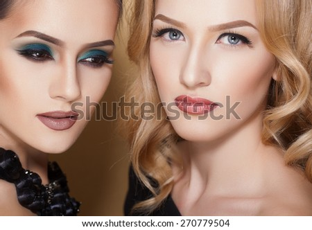 Two sexy and fashionable women with beautiful makeup, closeup shoot - stock photo