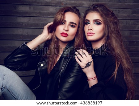 Two sexy beautiful woman with bright makeup, long hairstyle and in black jackets on wall background. Closeup fashion portrait