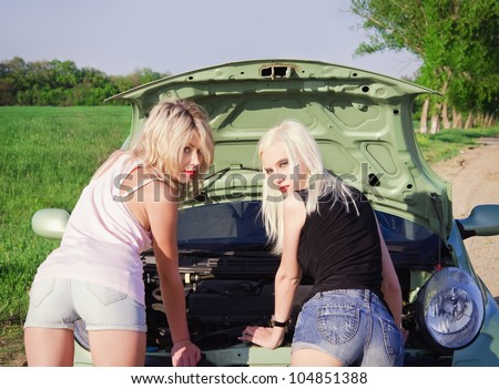 Two sexy blonde girls stand by the broken car and don't know what to do. Rear view
