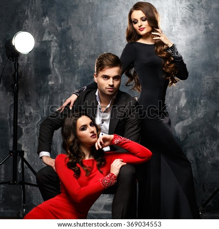 Two sexy elegant women in evening dresses and a handsome man in a suit. Beautiful women near the man.