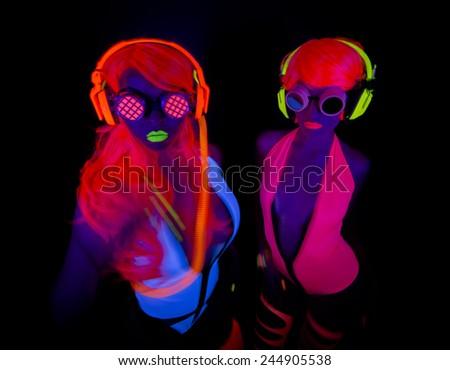 two sexy female disco dancers posing in UV costume - stock photo