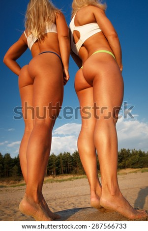 Two sexy girls posing on the beach.