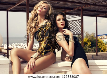 two sexy glamour girls posing on summer beach in fashion clothes