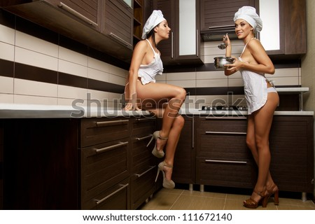 Two sexy housewives in kitchen room - stock photo