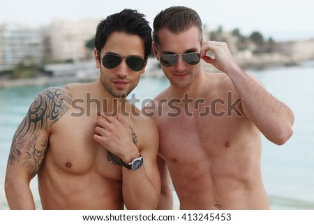Two sexy men posing on the beach