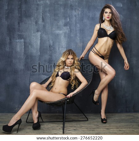 Two sexy models, beautiful blonde and brunette in underwear on a dark wall in the studio - stock photo