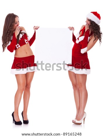 two sexy santa women holding and looking to a blank board on white background - stock photo