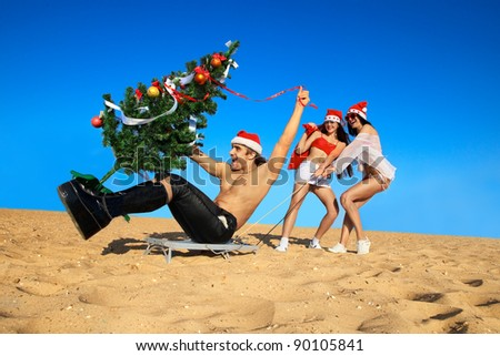 Two Sexy Santas  pulling Santa on a sled with Christmas tree at the beach.  (concept: Tropical winter fun)